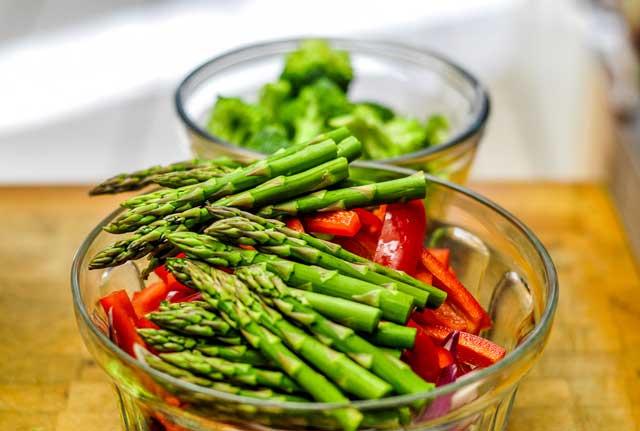 Ciotola di vetro con insalata di asparagi e peperoni rossi