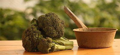 Broccoli su tavolo di legno vicino a pentola