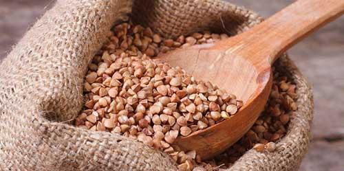 cucchiaio di legno in un sacco pieno di grano saraceno
