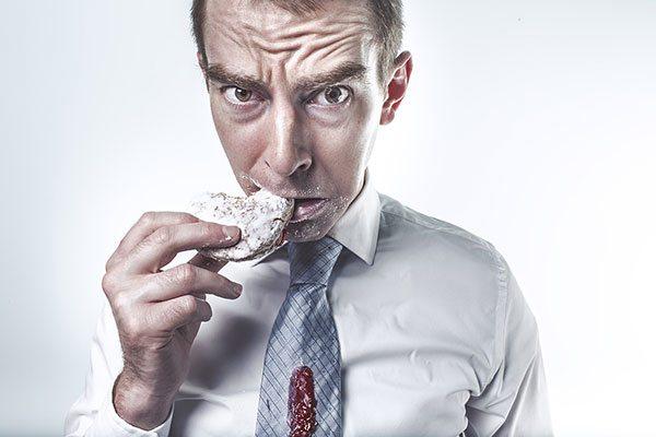 Uomo affranto che morde un biscotto pieno di zucchero