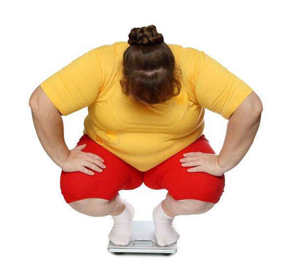 Donna obesa che si pesa