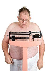 Uomo obeso che si pesa