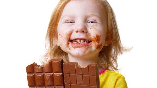 Bimba che mangia due grosse barrette di cioccolato