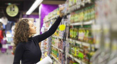 Ragazza che cerca alimenti con carboidrati complessi al supermercato.
